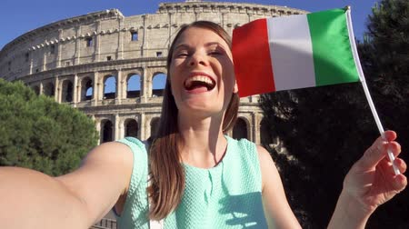 Woman doing selfie near famous attraction Colosseum in Rome, Italy. Teenage girl waving Italian flag in slow motion. Happy female tourist enjoying her european vacation. Student travel through Europe Stok Video