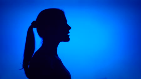 Silhouette of young frustrated woman crying. Females face in profile screaming in despair on blue background. Black contour shadow of teenagers half-face showing strong negative emotions