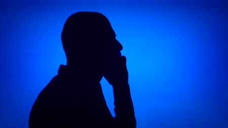 Silhouette of senior man using mobile on blue background. Males face in profile talking on cellphone. Black contur shadow of grandfathers half-face Stok Video