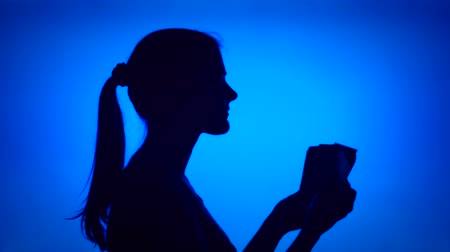 Silhouette of young successful woman count bundle of money on blue background. Females face in profile with pile of bills. Black contur shadow of teenagers half-face. Concept of wealth and success