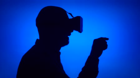 Black contour silhouette of senior man using VR 360 glasses make gestures with hands. Males face in profile on blue background. Seeing something exciting, learning to use contemporary technologies