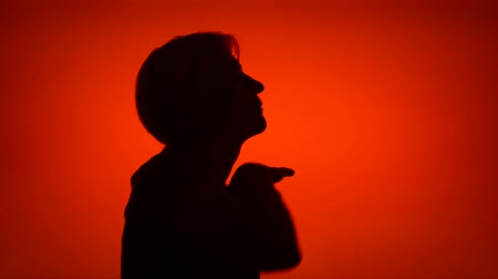 Silhouette of happy senior woman dancing silly on red background. Females face in profile having fun. Black contur shadow of grandmothers half-face fooling around