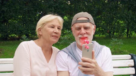 Senior couple sitting on bench in park cooling down with pink portable ventilator attached to mobile phone during heat. Happy family of retired pensioners enjoying summer vacation outdoors