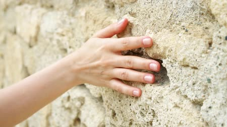 Woman sliding hand against old ancient stone wall in slow motion. Female hand touching hard rough surface of rock on sunny summer day Stock mozgókép