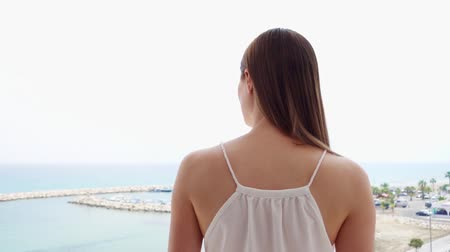 Smiling young woman in white dress enjoying sea view from terrace in morning. Female on vacation going out onto balcony in slow motion and looking at marina Stock mozgókép