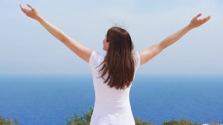 Smiling young woman in white t-shirt raising arms up at cliff against breathtaking view of blue sea. Carefree female outstretching hands in slow motion. Concept of freedom and inspiration