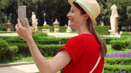 Woman in red dress and hat using mobile phone in green park in slow motion. Happy female tourist having video chat via online app in Villa Borghese. Student travel through Europe Stok Video