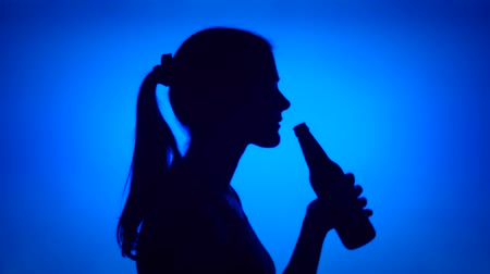 Silhouette of young woman opening can beer bottle on blue background. Females face in profile drinking beer from glass bottle. Black contur shadow of teenagers half-face