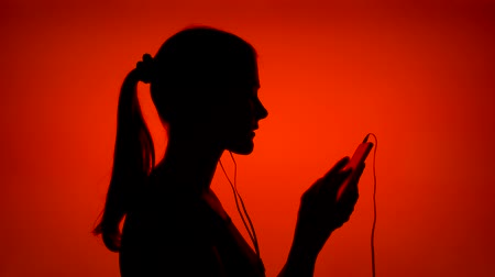 Silhouette of young woman listening to music on smart phone. Females face in profile putting on ear-phones on red background. Black contour shadow of teenagers half-face singing and dancing