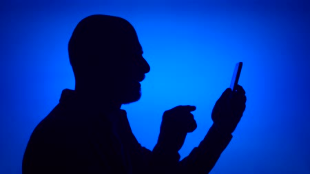 Silhouette of senior man using mobile on blue background. Males face in profile having video chat via online app on cellphone. Black contur shadow of grandfathers half-face Stok Video