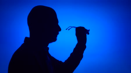 Silhouette of senior man with eyeglasses. Males face in profile putting on glasses on blue background. Black contour shadow of grandfathers half-face holding spectacles Stok Video