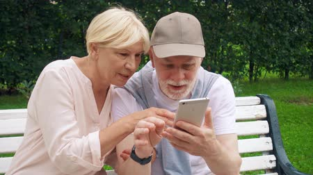Senior couple having great time sitting on bench in park chatting relaxing, browsing in smart phone. Happy family of retired pensioners enjoying summer vacation outdoors Stok Video