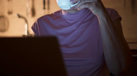Senior woman drink coffee from cup while read news on laptop. Freelancer use computer at night work from home office. Overworked businesswoman work on project in kitchen in evening. Camera moving up