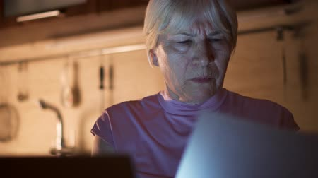 Senior woman relax at home reading news on laptop. Fenale freelancer use computer at night work hard from home office to meet deadline. Overworked businesswoman work on project in kitchen in evening