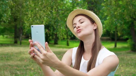 Young female student in white shirt sitting on grass on college campus doing selfie on mobile phone. Tourist in hat make photos on smart phone in public park enjoying summer sunny day
