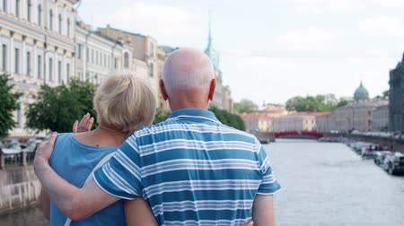 Back view of senior couple standing on embankment of canal looking around city. Happy loving pensioners traveling in Saint Petersburg, Russia. Hand-held camera