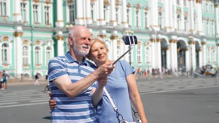 Senior couple on Palace Square do selfie with mobile phone and and self-stick on vacation. Happy loving pensioners travel in Saint Petersburg, Russia. Winter Palace on background. Hand-held camera