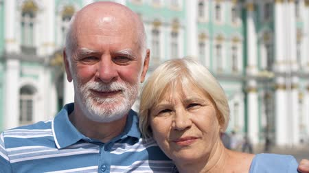 winter palace : Portrait of happy senior couple standing on Palace Square looking at camera. Happy loving pensioners traveling in Saint Petersburg, Russia. Winter Palace on background. Hand-held camera