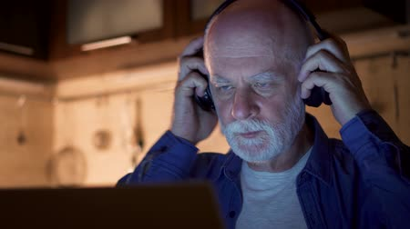 Senior man putting on big black wireless headphones. Male freelancer using laptop at night from home office while listening to music. Overworked businessman working on project in kitchen in evening