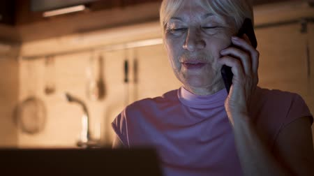 Senior woman working on laptop from home office in evening. Smiling retired female freelancer using mobile phone to discuss project with colleague at night. Overworked businesswoman in kitchen at home Stok Video