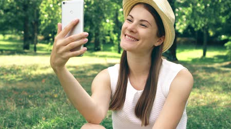 Young female student in white shirt sitting on grass on college campus using mobile phone. Tourist in hat having video chat via online app on cellphone in public park enjoying summer sunny day Stok Video
