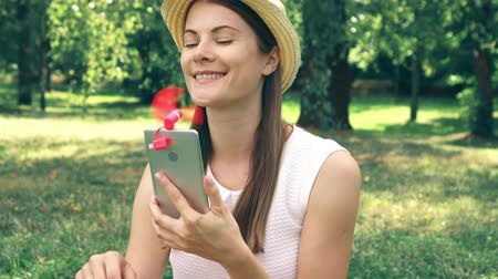 Female student sitting on grass on college campus using pink portable ventilator attached to mobile phone during heat. Tourist in hat cooling down with small fan working from smartphone in public park