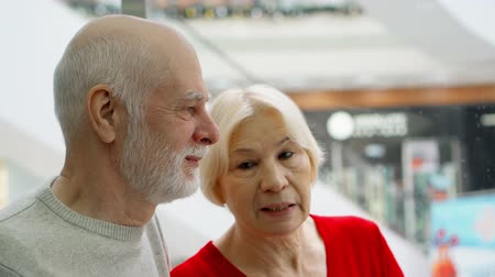 Senior couple in mall riding elevator. Pensioners in shopping center moving down in lift. Hand-held camera