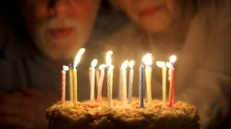 Loving senior couple celebrating anniversary with cake at home in the evening. Happy elderly family hugging, cuddling together, make wishes and blowing out candles in slow motion. Focus on the cake.