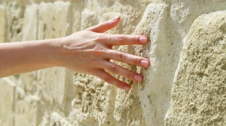Woman sliding hand against old ancient stone wall in slow motion. Female hand touching hard rough surface of rock on sunny summer day Wideo