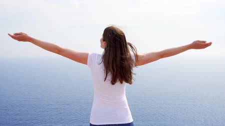 Smiling young woman in white t-shirt raising arms up at cliff against breathtaking view of blue sea. Carefree female outstretching hands. Concept of freedom and inspiration