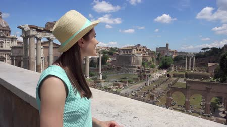 Woman in hat looking at ancient ruins Forum Romanum in slow motion. Happy female tourist enjoying vacation near Roman forum in center of Rome, Italy. Student travel through Europe