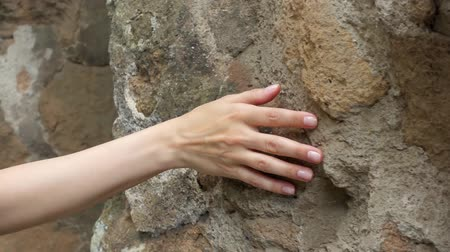 press wall : Woman sliding hand against old ancient stone wall in slow motion. Female hand touching hard rough surface of rock with green mold on it