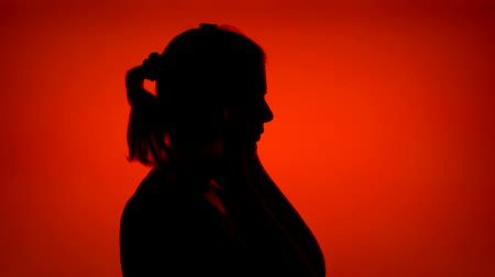 Silhouette of young woman listening to music. Females face in profile removing big black wireless headphones on red background. Black contour shadow of teenagers half-face singing Wideo