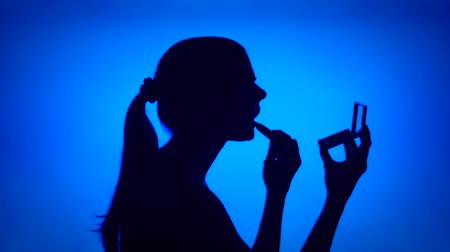 Silhouette of young woman applying lipstick on her lips on blue background. Females face in profile with mirror. Black contur shadow of teenagers half-face. Concept of fashion and glamour