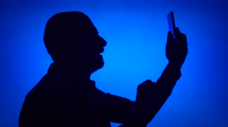 Silhouette of senior man using mobile phone on blue background. Males face in profile doing selfie on cellphone. Black contur shadow of grandfathers half-face making photos on smart phone