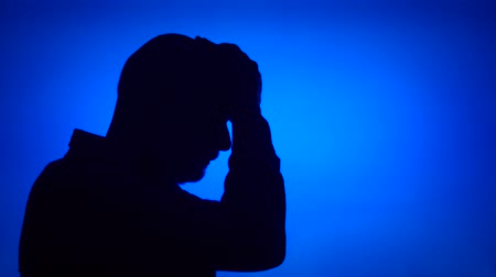 Silhouette of senior frustrated man. Sad males face in profile in despair on blue background. Black contour shadow of sad grandfathers half-face showing strong negative emotions