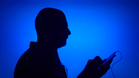 Silhouette of senior man listening to music on smart phone. Males face in profile putting on ear-phones on blue background. Black contour shadow of grandfathers half-face singing and dancing