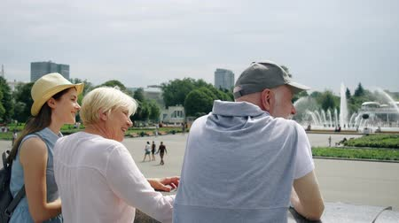 Back view of happy family enjoying summer vacation together in Moscow, Russia. Seniors with young teenage daughter having great time standing in Gorky Park laughing and chatting sightseeing Wideo