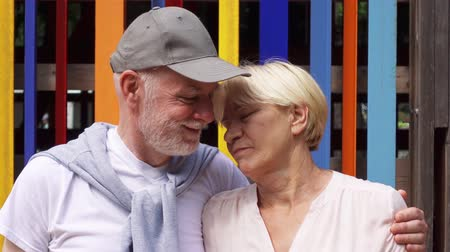 Portrait of happy smiling hugging senior couple standing against colored wall background. Carefree tourist family of retired pensioners enjoying vacation outdoors together