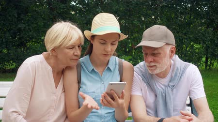 Seniors and their teenage daughter having great time sitting on bench in park chatting relaxing, browsing in mobile phone. Happy family enjoying vacation together looking for direction on online map