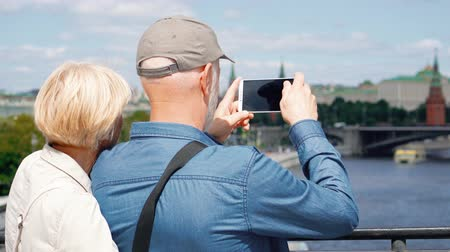 Back view of senior couple stand on observation deck take photos of city on mobile phone. Pensioners travelein Russia view attractions. Moscow city landscape and river on background. Hand-held camera