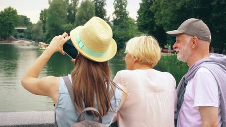 Back view of happy family enjoying summer vacation together in Moscow, Russia. Seniors with young teenage daughter having great time standing by lake in park take photos on mobile phone