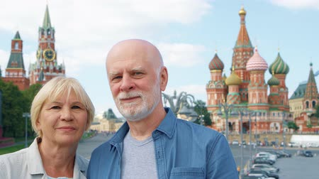 Portrait of senior couple stand on Basils Descent looking at camera. Pensioners traveling in Moscow, Russia. Red Square, St. Basils Cathedral and Kremlin clock tower on background. Hand-held camera