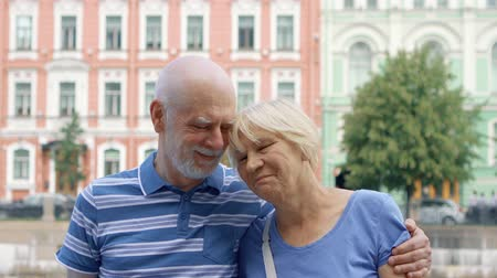 Portrait of happy senior couple standing on quay of canal looking at camera. Happy loving pensioners traveling in Saint Petersburg, Russia. Hand-held camera Wideo