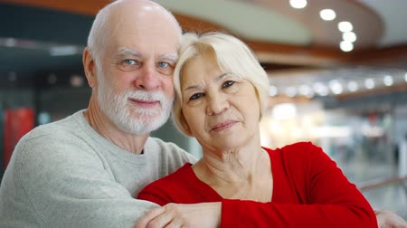 Portrait of senior couple standing in mall looking at camera. Loving hugging pensioners in shopping center smiling. Shop-windows with dummys on background. Hand-held camera