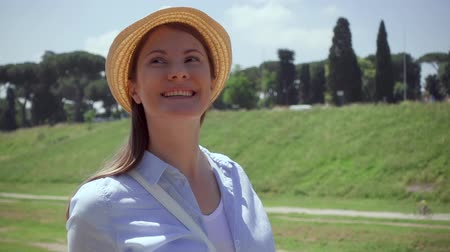 Slow motion of young woman with hat walking in european city. Happy female traveler enjoying vacation in Rome, Italy. Smiling girl on Circus Maximus. Concept of new experience and freedom in traveling Wideo