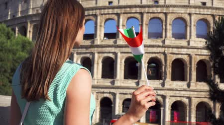 Young woman standing near famous attraction Colosseum in Rome, Italy. Teenage girl waving Italian flag in slow motion. Happy female tourist enjoying european vacation. Student travel through Europe