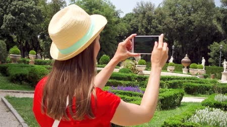 Woman in red dress and hat taking photo of beautiful green park on mobile phone in slow motion. Happy female tourist taking picture in Villa Borghese. Student travel through Europe