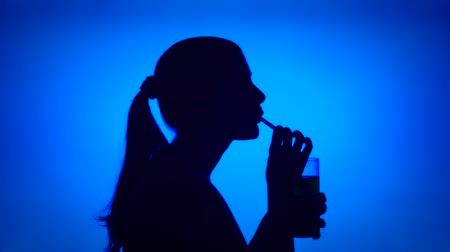 Silhouette of young woman drinking juice through straw on blue background. Females face in profile with glass of beverage. Black contur shadow of teenagers half-face