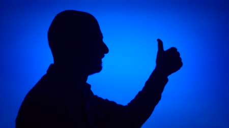 Silhouette of senior man making thumb up gesture on blue background. Males face in profile showing thumbs-up sign. Black contur shadow of grandfathers half-face. Success and achievement concept